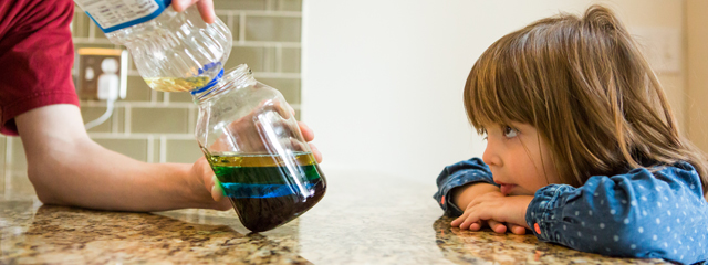 Pouring the vegetable oil into the Mason jar, resting on top of the green liquid.
