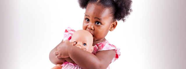 A black female toddler holds a white baby doll.