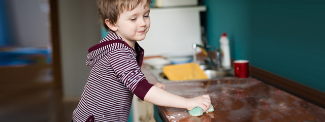 An older toddler washes the countertops in the kitchen.
