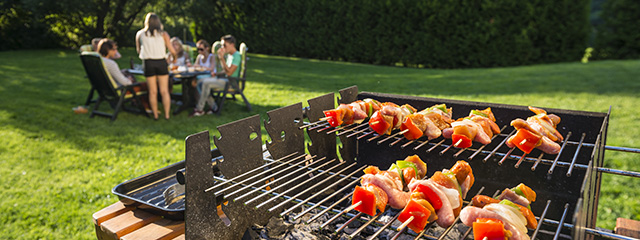 Healthy Grilling Recipes for Memorial Day Weekend | Most people love good barbecue. On this Memorial Day weekend, expand your repertoire to include healthy grilling recipes that will have the kids begging for seconds. | A family gathers outside at a table in the lawn while kebabs are cooking on the grill.