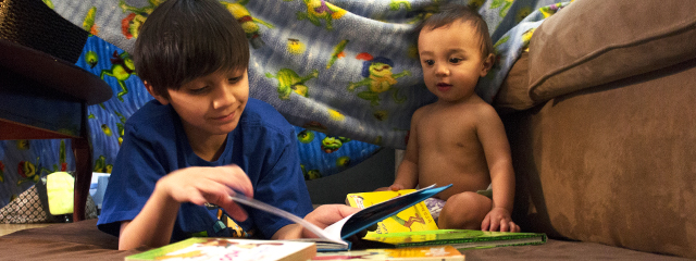 The author's one-year-old son and her 11-year-old step son play in a DIY fort.