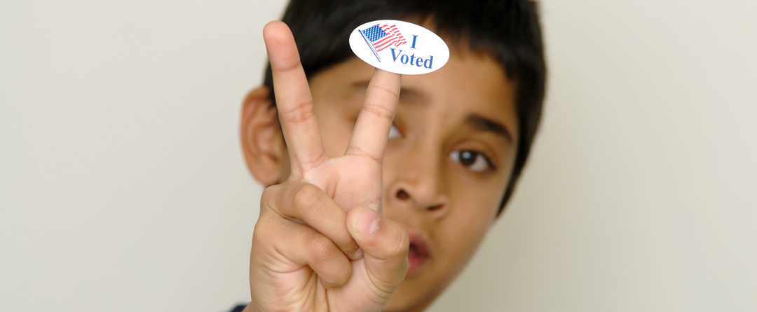 "Happy Birthday! You can vote now. | A teen shows his ""I Voted"" sticker."