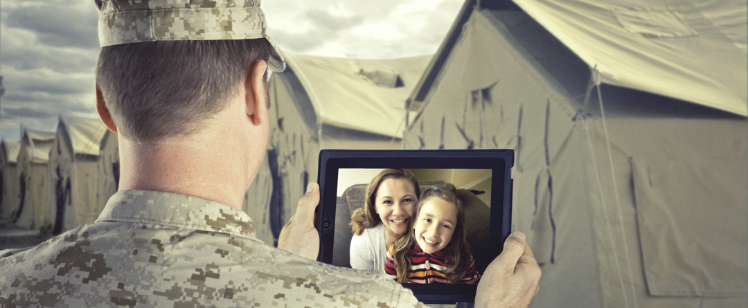 How to Be An Engaged Parent While Deployed | A soldier chats with his family on a tablet.