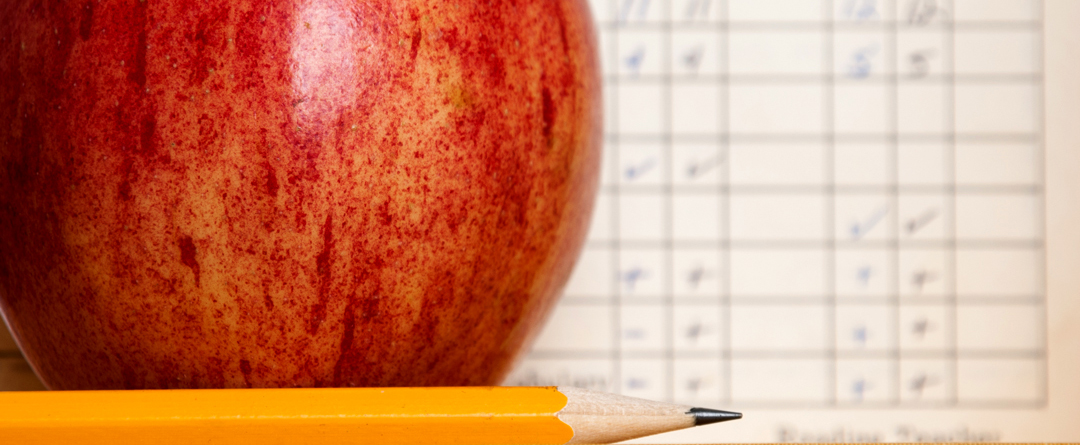 Standards-Based Report Cards + the Common Core | An apple and pencil sit on the desk in front of a grading scale.