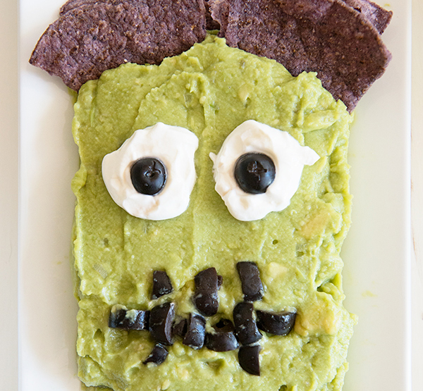 5 Healthy and Creative Halloween Party Foods | Frankenguac, recipe and photo via Dine and Dish | Frankenstein's face is made of guacamole, with blue corn chips serving as hair, sour cream as eyeballs, and olives as pupils and the mouth.