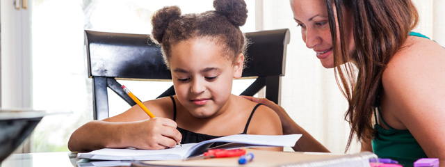 5 Tips to Help Your Children With Homework | Help your child with their homework with these tips, even if you don't know the material yourself. Great parent engagement tips. | This image shows a young girl sitting at the table working on homework while her mother looks on.