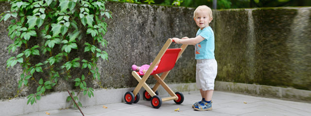 Gender Neutral Parenting | A young boy smiles as he pushes a stroller with a doll inside it.