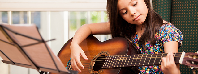 Whistle While You Learn: How Learning Music Can Improve Your Child's Brain | Learning to play music by age seven can help a child's brain develop stronger, help them learn a better vocabulary, teach them to focus, and more. | A girl practices guitar.