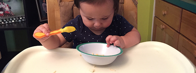 4 Fun Ways to Develop Your Toddler's Fine Motor Skills | As infants enter the early toddler stage, we tend to focus on major milestones like crawling, walking, and running (gross motor skills). But fine motor skills are equally as critical. Here are 4 fun ways to develop those skills. | The author's daughter eats her food with a spoon.