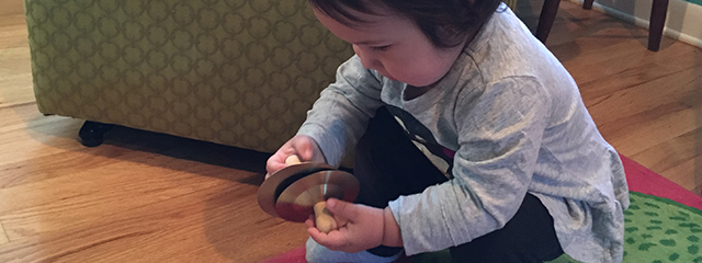 4 Fun Ways to Develop Your Toddler's Fine Motor Skills | As infants enter the early toddler stage, we tend to focus on major milestones like crawling, walking, and running (gross motor skills). But fine motor skills are equally as critical. Here are 4 fun ways to develop those skills. | The author's daughter plays with cymbals.