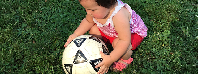 4 Fun Ways to Develop Your Toddler's Fine Motor Skills | As infants enter the early toddler stage, we tend to focus on major milestones like crawling, walking, and running (gross motor skills). But fine motor skills are equally as critical. Here are 4 fun ways to develop those skills. | The author's daughter picks up a soccer ball.