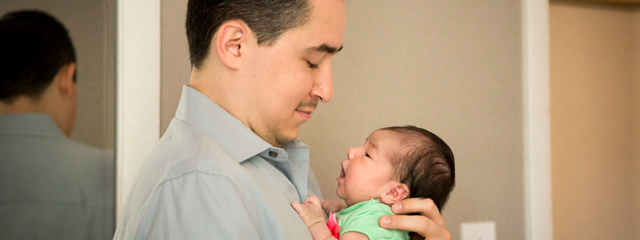 Best Practices for Infant Care From a New Dad | Author Mario Vela looks at his newborn daughter, Mariana, as he holds her.