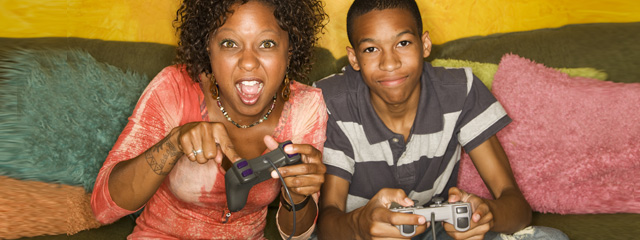 A mother enthusiastically plays a video game with her teenage son.