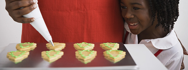 How can we start a holiday tradition for our own family? | A young girl helps her mother make holiday cookies.