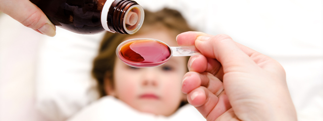How can I keep my daughter healthy at school? | A parent measures cough syrup for a young child, who lays in bed.