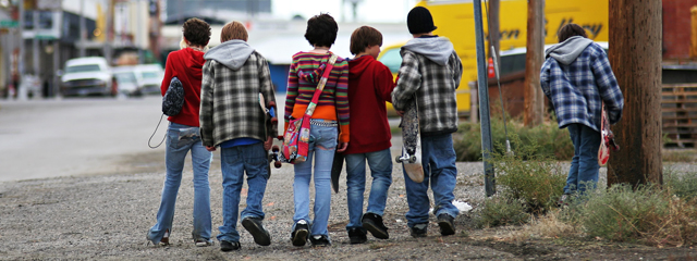 A group of middle school kids walk to school on a city street.