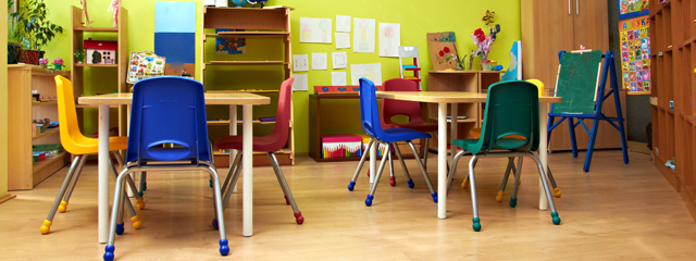 A empty colorful classroom with green walls, yellow, blue, and red chairs.