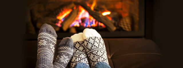 A couple's feet warm up by the fire.