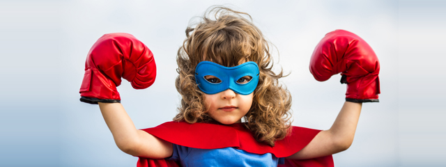 A young girl flexes her muscles in superhero garb.