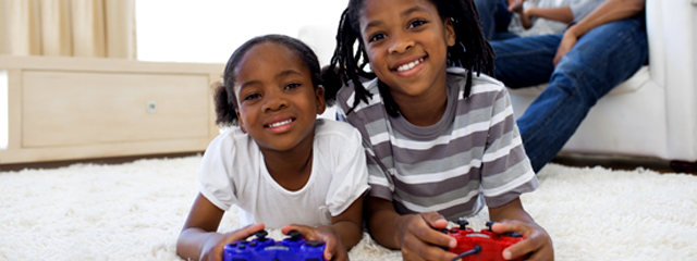 Two kids smile as they play video games.