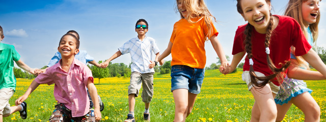Children run through a field holding hands and smiling.