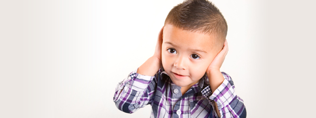 A young boy covers his ears.